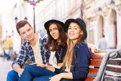 Tres amigos que se sientan junto en el banco Fotos de archivo libres de regalías