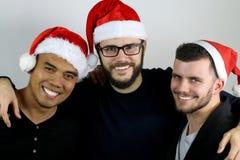 Tres amigos que sonríen para la Navidad Imágenes de archivo libres de regalías
