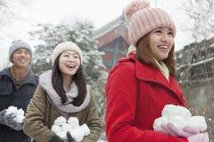 Tres amigos que sostienen bolas de la nieve en nieve en parque fotos de archivo libres de regalías