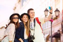 Tres amigos que toman el selfie con el teléfono móvil Imagen de archivo