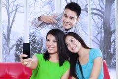 Tres amigos que toman la imagen con el teléfono móvil Fotos de archivo