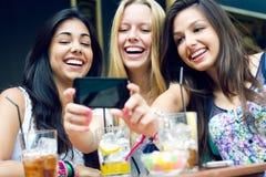 Tres amigos que toman las fotos con un smartphone Fotografía de archivo libre de regalías