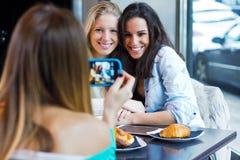 Tres amigos que toman las fotos con un smartphone Imágenes de archivo libres de regalías