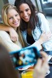 Tres amigos que toman las fotos con un smartphone Fotografía de archivo