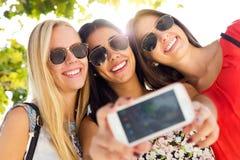 Tres amigos que toman las fotos con un smartphone Fotos de archivo libres de regalías