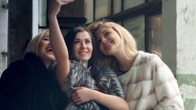 Tres amigos que toman las fotos con un smartphone almacen de video