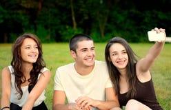 Tres amigos que toman las fotos exteriores y la sonrisa foto de archivo libre de regalías