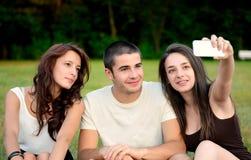 Tres amigos que toman las fotos exteriores y la sonrisa Imagen de archivo