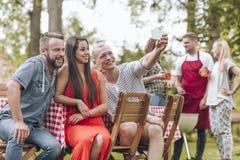 Tres amigos que toman un selfie durante un outsid del partido de la parrilla del verano foto de archivo libre de regalías