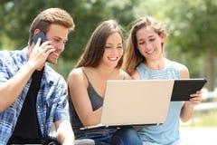 Tres amigos que usan los dispositivos múltiples en un parque imágenes de archivo libres de regalías