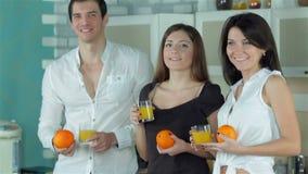 Tres amigos refrescan para arriba con el zumo de naranja almacen de video