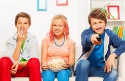 Tres amigos sonrientes comen las palomitas juntas en el sofá Foto de archivo libre de regalías
