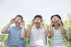 Tres amigos sonrientes en fila que soportan pelotas de golf delante de sus ojos foto de archivo libre de regalías
