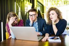 Tres amigos trastornados en línea usando un ordenador portátil con problemas y emociones tristes en una cafetería Imagen de archivo libre de regalías