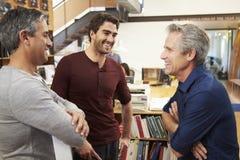 Tres arquitectos de sexo masculino que charlan en oficina moderna junto Imagen de archivo libre de regalías
