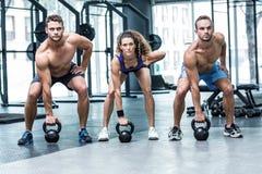 Tres atletas musculares alrededor para levantar una campana de la caldera Foto de archivo