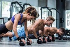 Tres atletas musculares en una posición del tablón Fotografía de archivo
