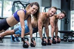 Tres atletas musculares en una posición del tablón Imagen de archivo libre de regalías