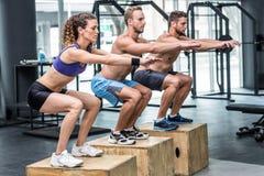 Tres atletas musculares que hacen posiciones en cuclillas de salto Foto de archivo libre de regalías