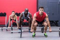 Tres atletas musculares que levantan barbells Imagen de archivo