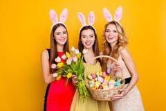 Tres atractivos, muchachas bonitas que llevan los oídos del conejito que llevan a cabo el bouque Imagen de archivo