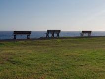 Tres bancos de parque que miran hacia fuera al mar imágenes de archivo libres de regalías
