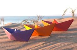 Tres barcos de papel en una playa: Púrpura, naranja y rojo Imagenes de archivo
