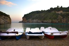 Tres barcos del pedal con el toldo doblado que se alinea a lo largo de la orilla Dos acantilados que se colocan cerca del frente  imagenes de archivo