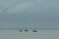 Tres barcos del tirón en el mar. Imagen de archivo libre de regalías