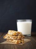 Tres barras de granola en el pergamino con leche en fondo de madera rústico Fotografía de archivo libre de regalías