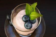 Tres bayas frescas de arándanos en yogur con las hojas de menta Fotos de archivo