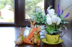 Tres bebés del conejo tienen raíces en sus manos Rosas blancas artificiales plantadas dentro de la taza Suvinir tres niños del co Foto de archivo libre de regalías