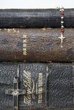 Tres biblias apiladas antigüedad con el rosario antiguo de dos cruces encendido Foto de archivo libre de regalías