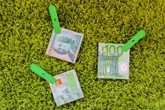 Tres billetes de banco verdes en clavijas de ropa verdes en el fondo verde Imagen de archivo