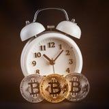 Tres bitcoins y despertador blanco del vintage que brilla intensamente en fondo negro Fotografía de archivo