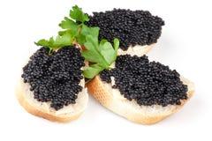 Tres bocadillos con el caviar negro aislado Fotos de archivo