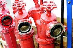 Tres bocas de incendios rojas con las válvulas están en el almacén imagen de archivo libre de regalías