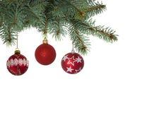 Tres bolas brillantemente coloreadas de la Navidad que cuelgan en el árbol de navidad Fotos de archivo libres de regalías