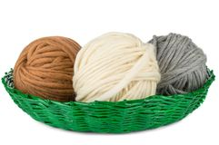 Tres bolas de hilado en cesta verde en el fondo blanco Imagen de archivo libre de regalías