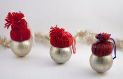Tres bolas de la decoración de la Navidad con los sombreros rojos hechos a mano Imágenes de archivo libres de regalías