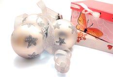Tres bolas de la Navidad con la cinta y los regalos de plata Foto de archivo libre de regalías