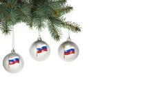 Tres bolas de la Navidad con la imagen del estado ruso señalan la ejecución por medio de una bandera en un árbol de navidad Foto de archivo
