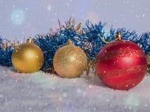 Tres bolas de la Navidad en la nieve Invitación del Año Nuevo Fotografía de archivo libre de regalías