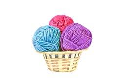 Tres bolas multicoloras de hilado en la cesta Fotografía de archivo
