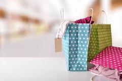 Tres bolsos coloreados con nueva ropa dentro en una alameda Fotografía de archivo