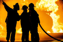 Tres bomberos que luchan un fuego ardiente Fotografía de archivo libre de regalías
