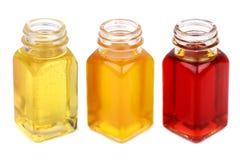 Tres botellas con aceites se cierran para arriba aislado en blanco Fotos de archivo