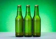 Tres botellas de cerveza en blanco mojadas Imagenes de archivo