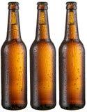 Tres botellas de cerveza fría con descensos condensados grandes foto de archivo