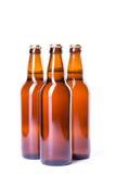 Tres botellas de cerveza helada aisladas en blanco Imagen de archivo
